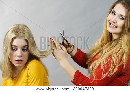 Hairstyle and haircut. Young female barber holding scissors tool ready to trimming hair her friends. Two girls creating new hairdo coiffure poster