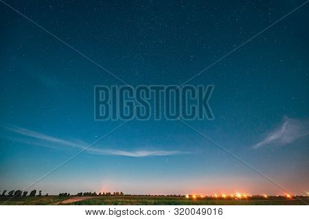 Night Starry Sky With Glowing Stars Above Landscape With City Lights. Night Starry Sky Above Ground.