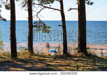 A Guy And A Girl Relax On A Sandy Beach In The Dunes Of The Baltic Sea On A Warm Summer Day