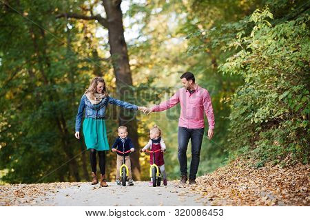 Beautiful Young Family With Small Twins On A Walk In Autumn Forest.