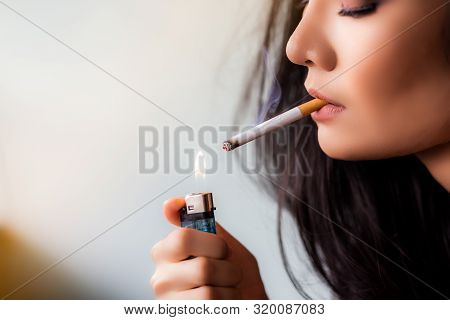 Charming Beautiful Young Asian Woman Use Cigarette Lighter For Lighting Cigarette In Her House. Attr