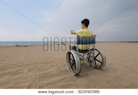 Young Boy On The Wheelchair In The Sandy Beach In Summer