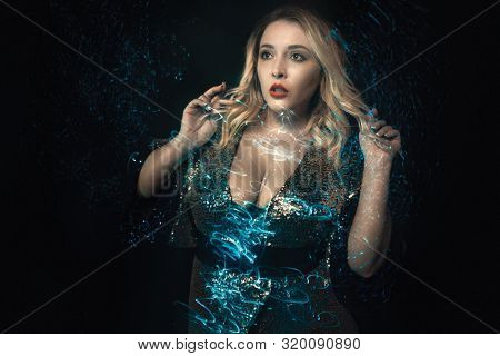 Fashion portrait of young woman in shiny decollete evening dress. Mixed blue lights effects. Close-up blonde in sequins wear. Stylish glamour look. Expression of surprise on face. Black background.