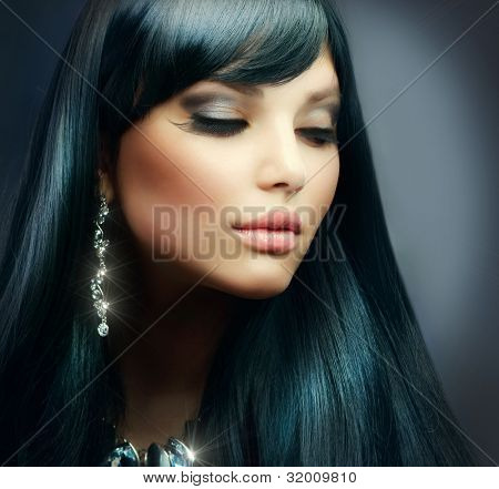 Beautiful Brunette Girl. Healthy Long Hair and Holiday Makeup. Jewelry
