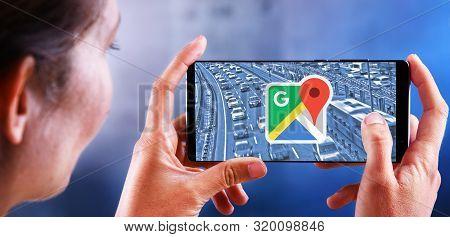 Poznan, Pol - Jul 10, 2019: Woman Holding Smartphone Displaying Logo Of Google Maps, A Web Mapping S