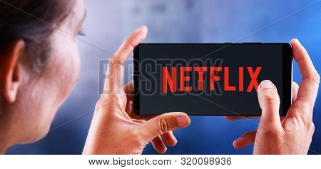 Poznan, Pol - Jul 10, 2019: Woman Holding Smartphone Displaying Logo Of Netflix, An American Media-s