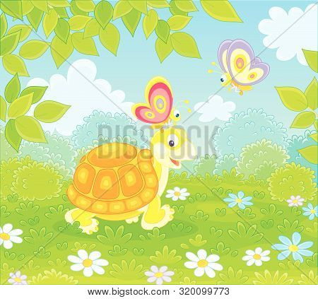 Friendly Smiling Turtle Playing With Small Colorful Butterflies On Green Grass Of A Forest Glade On