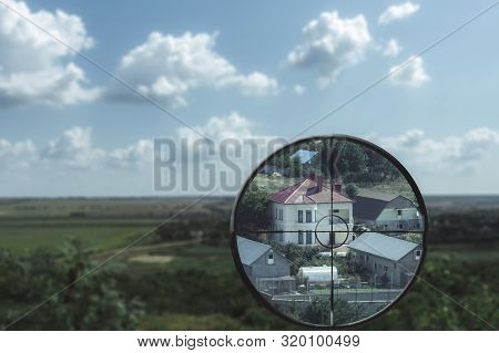 A Magnified View Of A House In The Valley In A Snipers Optical Sight. Killer Looks Into The Optical