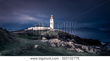 A Picturesque Lighthouse On The Rocky Coast Of The Seascape In Ireland.