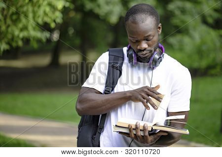 Portrait Of Black Student Youngster With Daypack Flipping Book Pages In Campus Park