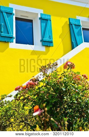 Sunny View Of Ayellow House With Blue Shutters, With A Bush Of Pink Flowers And Many Blossoms Growin