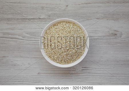 Organic Arborio Rice In A White Bowl On A White Wooden Background, Top View. Flat Lay, Overhead, Fro