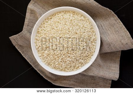 Organic Arborio Rice In A White Bowl On A Black Background, Overhead View. Flat Lay, Top View, From