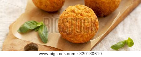 Homemade Fried Arancini With Basil On A Rustic Wooden Board, Low Angle View. Italian Rice Balls. Clo