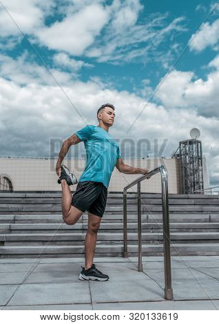 Athlete Guy Doing Knee And Leg Muscle Stretch Before Training. In The Summer In The City, Preparing