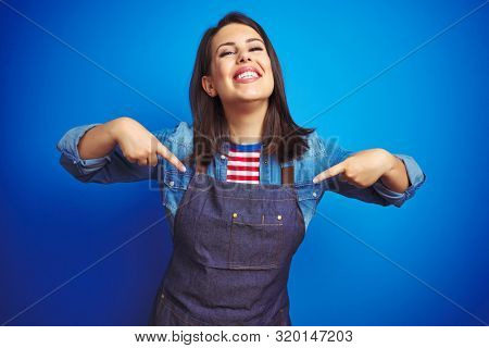 Young beautiful business woman wearing store uniform apron over blue isolated background looking confident with smile on face, pointing oneself with fingers proud and happy.