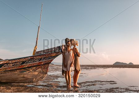 Two Beautiful Young Fashion Models On The Beach At Sea Boat