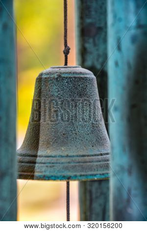 A weathered bell wind chime, sitting still on a calm day poster