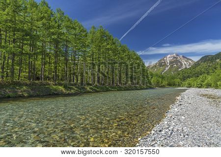 The Pristine Alpine Water Of Azusa River Flowing In Front Of Landscape View Of Mount Hotaka-dake On