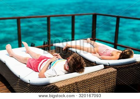 Kids enjoying tropical summer vacation relaxing at overwater villa in luxury resport