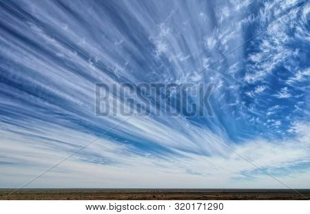 Long Streaky White Clouds With Blue Sky On A Sunny Day