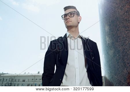 A portrait of a goodlooking young guy walking in the street. Men's beauty, fashion.