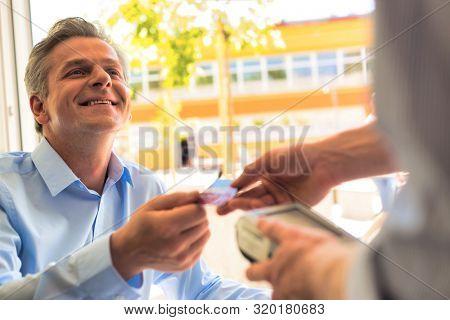 Smiling mature customer paying through credit card at restaurant