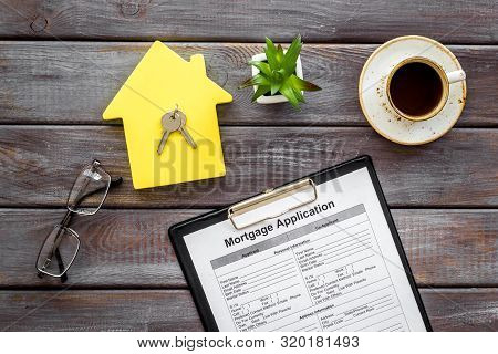 House Mortgage With Application, House Toy, Keys, Glasses, Coffee On Wooden Banker Desk Background T