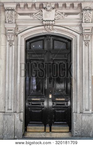 Sculptural Relief Arch Around Elegant Entrance To Antique Building In Paris France. Black Painted Wo