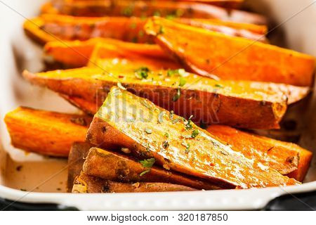 Baked Sweet Potato Slices With Spices In The Oven Dish. Healthy Vegan Food Concept.