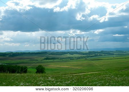 Landscape, Green Agricultural Fields On The Horizon Forest, And The Sky With Large Dark Cumulus Clou