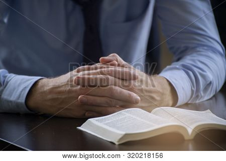 Pray And Bible Concept.hand In Hand Together On Bible By Man (worship Christian),thinking And Closed