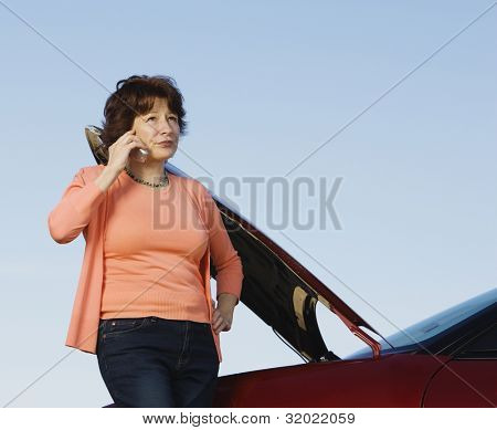 Unhappy woman on cell phone with car breakdown