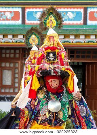 Lingdum, Sikkim, India - December 23, 2011: Lama In Ritual Costume And Ornate Hat Performs A Histori
