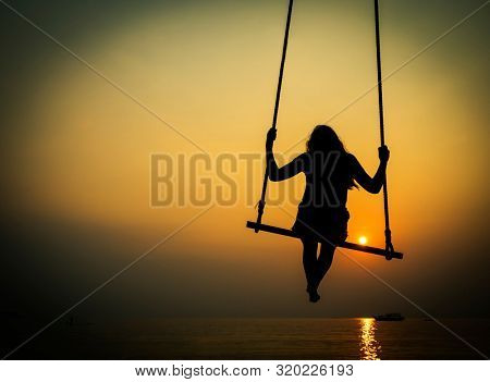 Teenager girl on a swing silhouette on a background of sunset sky and sea. Thailand, Southeast Asia