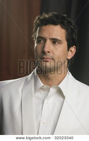 Portrait of Hispanic man wearing white tuxedo