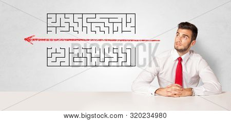 Businessman presenting a maze on a wall