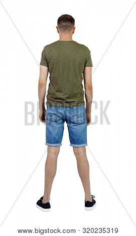 Back view of young manin shorts looking. Rear view people collection. backside view of person. Isolated over white background. The guy in sneakers looks forward.