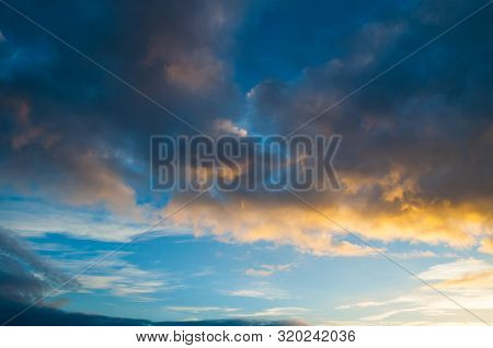 Blue dramatic sunset sky background - picturesque colorful sky clouds lit by sunlight. Vast sky landscape panoramic scene, sunset sky evening sunny view