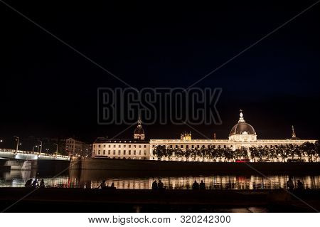 Lyon, France - July 17, 2019: French People Sitting At Night On The Riverbank Of The Quais De Rhone,