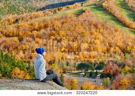 Woman hiking at Artist's Bluff in autumn. Fall colours in Franconia Notch State Park. White Mountain National Forest, New Hampshire, USA