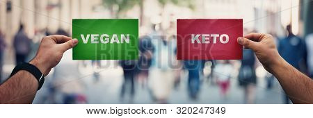 People Hands Holding Two Papers Over A Crowded Street Background Comparing Vegan Vs Ketogenic Diets.