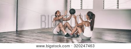Gym fit medicine ball partner workout fun exercises friends training together in fitness class panoramic banner. Couple training body core workout throwing weighted slam ball at each other.