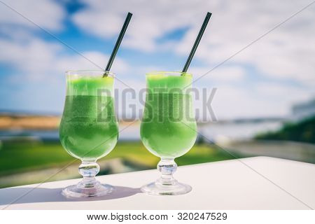 Green smoothies detox Healthy eating juice cleanse juices at cafe. Vegetarian diet juicing trend. Two glasses of spinach vegetable juice on outdoor restaurant table on summer background.
