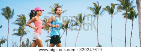 Healthy people fit active lifestyle couple running on palm trees tropical background panoramic banner. Happy friends exercising together -training buddy friend.