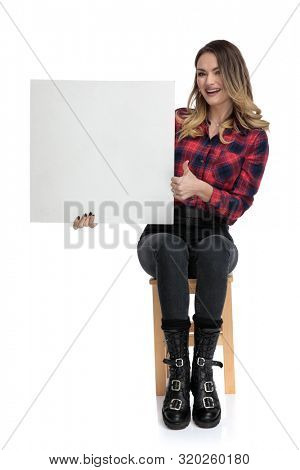 cute casual woman in checkered shirt and boots is sitting on a wooden chair and presenting a blank billboard thrilled with a thumbs up gesture on white studio background