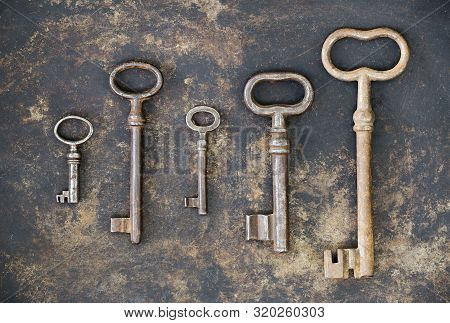 Escape game room concept, group of antique keys on rusty metal background
