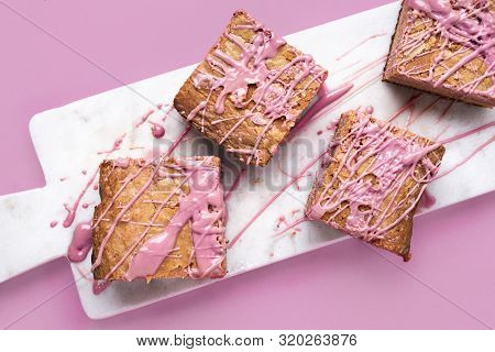 Pink Brownies With Ruby Chocolate On White Marble Cutting Board And Pink Background. Close-up Image