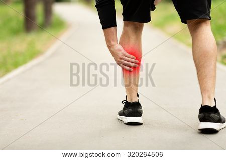 Male Athlete With Injured Calf, Massaging Painful Leg Muscle With Red Sore Spot Suffering From Traum