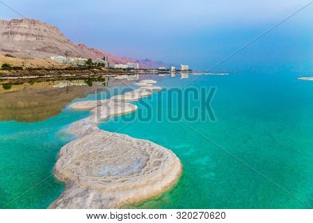 Azure sea water is full of healing salts. Small islets and path of salt in the water. Early morning at the resorts of the Dead Sea. Israel. Concept of ecological, medical and photo tourism
